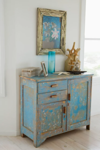 Blue desk with painting hanging on the wall above it.